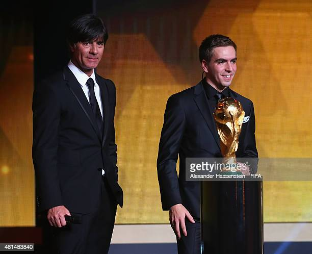 World Coach of the Year for Men's Football winner Joachim Loew of Germany and Philipp Lahm bring on the FIFA World Cup Trophy during the FIFA Ballon...