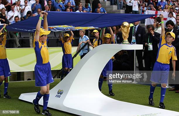 the FIFA flag bearers hold the FIFA flag above the trophy