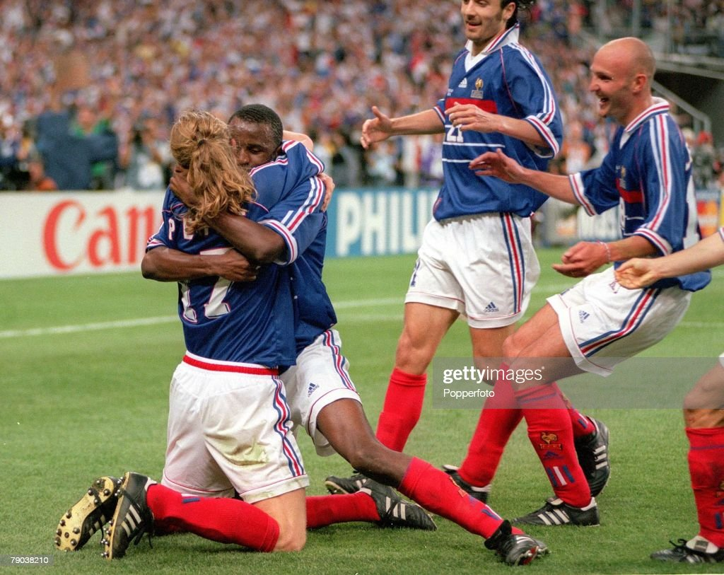 1998 World Cup Final. St. Denis, France. 12th July, 1998. France 3 v Brazil 0. France's Emmanuel Petit is hugged by teammate Patrick Vieira after he scored the third goal as other French players move in. : Photo d'actualité