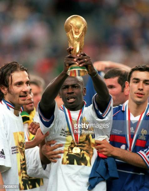 World Cup Final St Denis Paris France 12th July France 3 v Brazil 0 France's Lilian Thuram holds the World Cup trophy alongside Dugarry and Pires...
