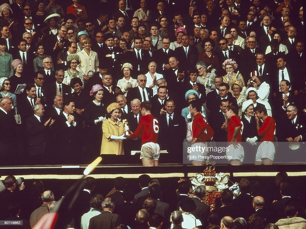 World Cup Final, 1966 Wembley Stadium, England. 30th July, 1966. England 4 v West Germany 2. England captain Bobby Moore receives the trophy from HRH Queen Elizabeth II after his team's win. : News Photo