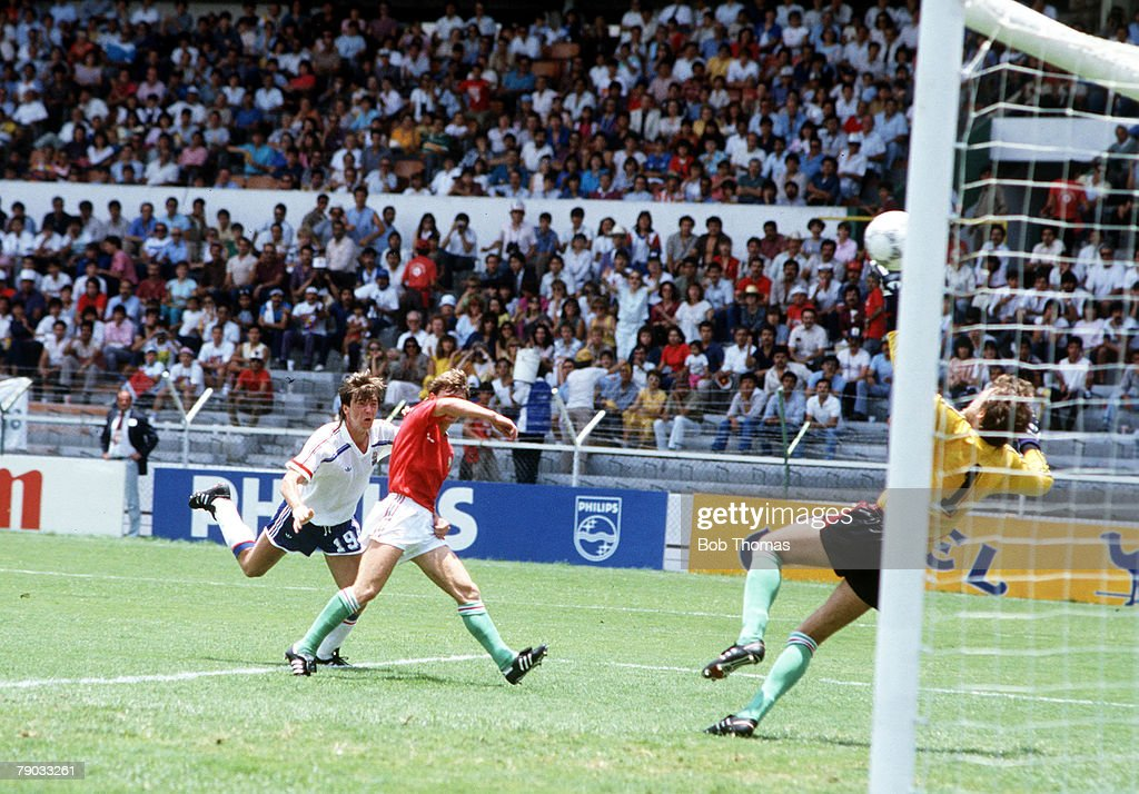 1986 World Cup Finals. Leon, Mexico. 9th June, 1986. France 3 v Hungary 0. France's Yannick Stopyra scores a goal past Hungarian defenders. : Photo d'actualité