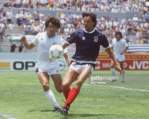 World Cup Finals Neza Mexico 13th June Scotland 0 v Uruguay 0 Scotland's Greame Sharp under pressure from Uruguay's Dario Pereyra as they go for the...