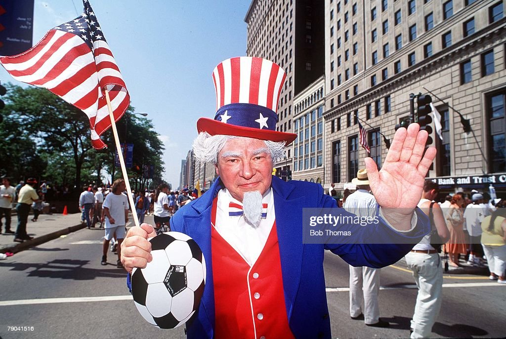 1994 World Cup Finals. Parade on Michigan Ave., Chicago. 15th June 1994. An American fan dressed up as Uncle Sam, wearing a hat in the team's colours and holding the stars and stripes flag during a parade in Chicago. : News Photo