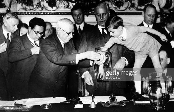 World Cup Finals Paris France FIFA president Jules Rimet is assisted by a young boy in making the draw for the World Cup