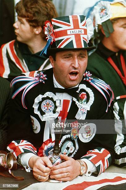 A World Cup football fan covered in badges ribbons and flags showing his support for Team England leans forward against a railing and shouts probably...