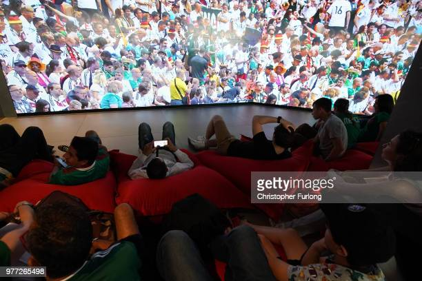 World Cup football fans watch the Germanyv Mexico game on a giant tv in the Moscow Audi dealership on Nikolskaya Street near Red Square on June 17...