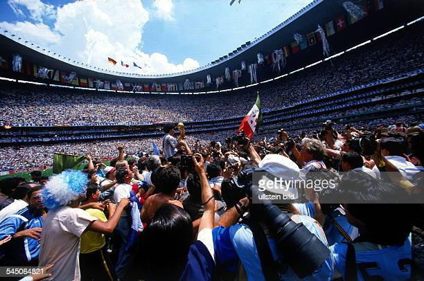 World Cup in Mexico Final in Mexico City: Argentina 3 - 2 Germany - Argentine captain Diego Maradona with the World Cup trophy amid photographers -