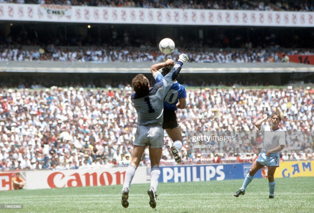 1986 World Cup Quarter Final, Azteca Stadium, Mexico, 22nd June, 1986, Argentina 2 v England 1, Argentina's Diego Maradona scores his side's first goal past English goalkeeper Peter Shilton by use of his hand, Maradona later claimed that the goal was scor : News Photo