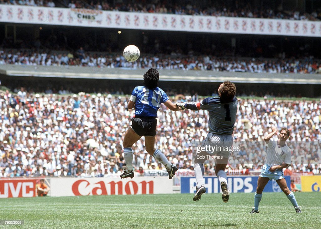 World Cup Quarter Final, Azteca Stadium, Mexico, 22nd June, 1986, Argentina 2 v England 1, Argentina's Diego Maradona scores his side's first goal past English goalkeeper Peter Shilton by use of his hand, Maradona later claimed that the goal was scored by 'The Hand Of God,'