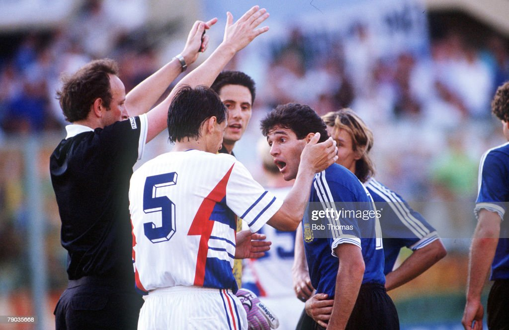 1990 World Cup Quarter Final. Florence, Italy. 30th June, 1990. Argentina 0 v Yugoslavia 0. (Argentina win 3-2 on penalties). Argentina's Jorge Burruchaga argues with Yugoslavia's Faruk Hadzibegic as the referee watches. : News Photo
