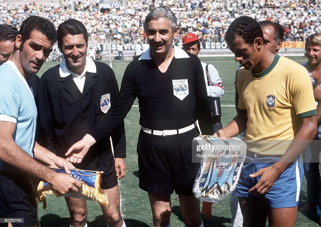 1970 World Cup Semi-Final Guadalajara, Mexico. 17th June, 1970. Brazil 3 v Uruguay 1. The Uruguayan captain exchanges pennants with Brazilian captian Carlos Alberto (R) before the match as referee De Mendibil (2L) and linesman Bakhramov looks on. : News Photo