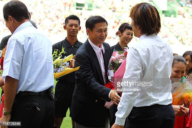 World Cup winning heam coach Norio Sasaki of Japan receive flowers prior to the Nadeshiko League match between INAC Kobe Leonessa and JEF United...