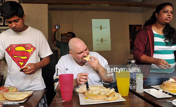 World Eating champion Dale Boone of the US and others eat hamburgers during the Final Asian Contest of 2012 'Eating Season' organised by WLOCE in...