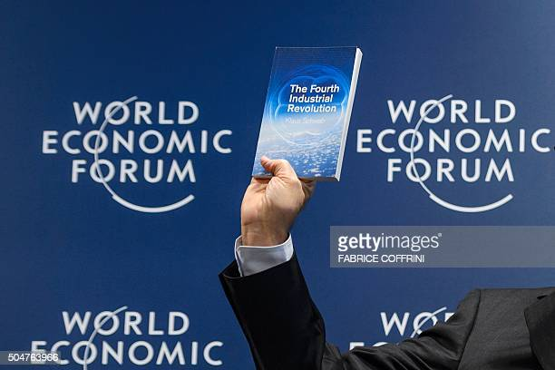 World Economic Forum founder and executive chairman Klaus Schwab shows a book he wrote during a news conference on the programme of the Davos World...
