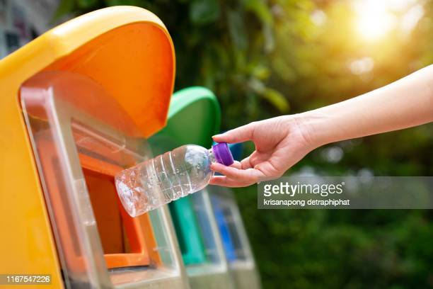 world environment day concept. woman hand holding and putting plastic bottle waste into garbage trash. - jetée photos et images de collection