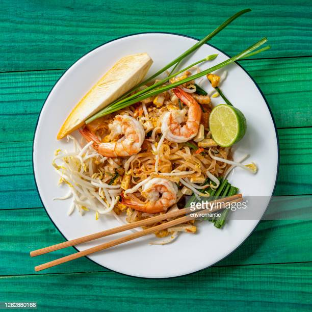 world famous freshly stir-fried cooked, thai recipe of prawn pad thai noodles on a round traditional enameled metal dish with chopsticks laid on the side of the dish, set on an abstract weathered turquoise colored wood panel table background. - thai food stock pictures, royalty-free photos & images