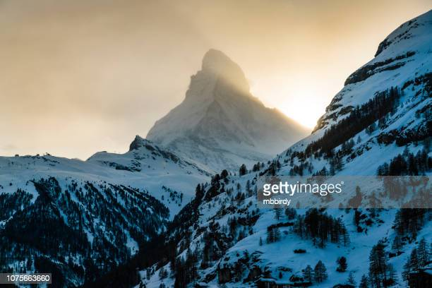 world famous mountain peak matterhorn above zermatt town switzerland, in winter - zermatt stock pictures, royalty-free photos & images