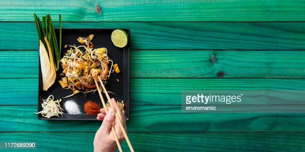 world famous thai recipe of prawn pad thai noodles with a man eating the meal with chopsticks, the meal is on a dish on an old abstract weathered turquoise colored wood panel table background. - bean sprout stock pictures, royalty-free photos & images