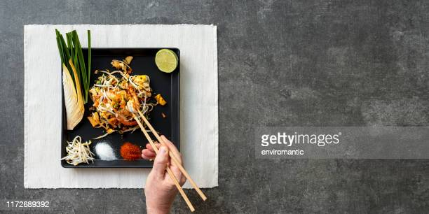 world famous thai recipe of prawn pad thai noodles with a man eating the meal with chopsticks, the dish set on a placemat on a concrete textured table background. - stir fried stock pictures, royalty-free photos & images