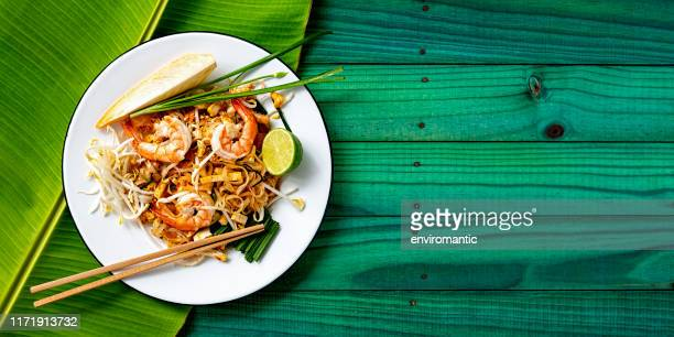 world famous thai recipe of prawn pad thai noodles with chopsticks on a dish and banana leaf on a turquoise colored old wood panel table background. - noodles stock pictures, royalty-free photos & images