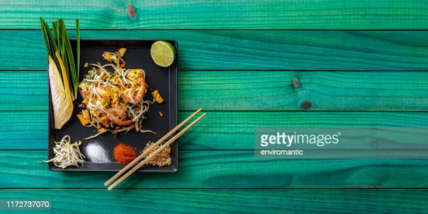 world famous thai recipe of prawn pad thai noodles with chopsticks on a dish and banana leaf on an old turquoise wood panel table background. - noodles stock pictures, royalty-free photos & images