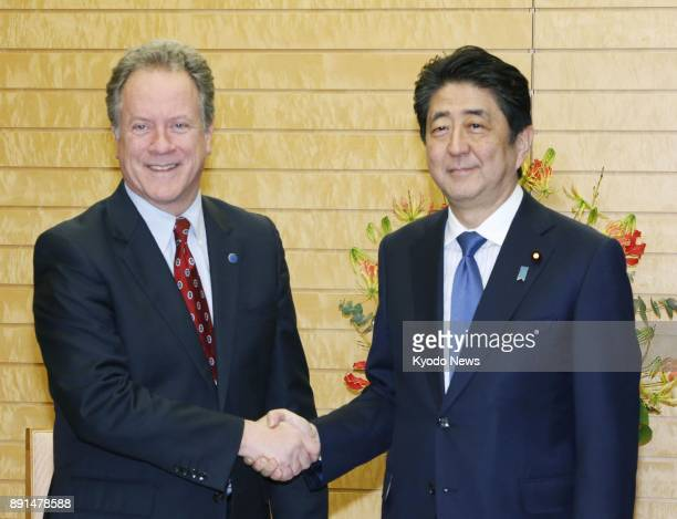 UN World Food Program head David Beasley and Japanese Prime Minister Shinzo Abe shake hands at Abe's office in Tokyo on Dec 12 2017 The two agreed to...