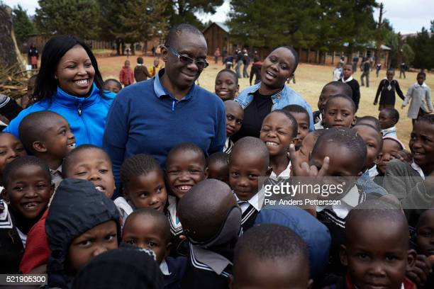 World Food Program staff stands with pupils at Masapong primary school on September 1 in Masapong district outside Maseru Lesotho The are given two...