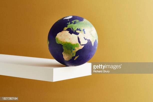 a world globe balanced on the edge of a shelf - richard drury stock pictures, royalty-free photos & images