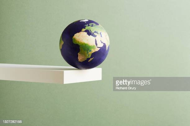 a world globe balanced on the edge of a shelf - global stock pictures, royalty-free photos & images