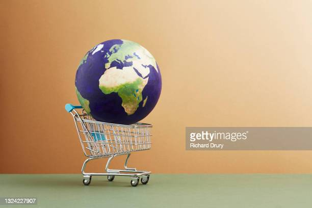 a world globe in a shopping trolley - navigational equipment stock pictures, royalty-free photos & images