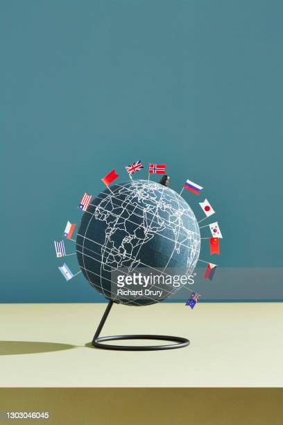 a world globe marked with several national flag pins - politics and government stock pictures, royalty-free photos & images