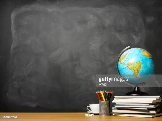 World globe on books on school teacher's desk