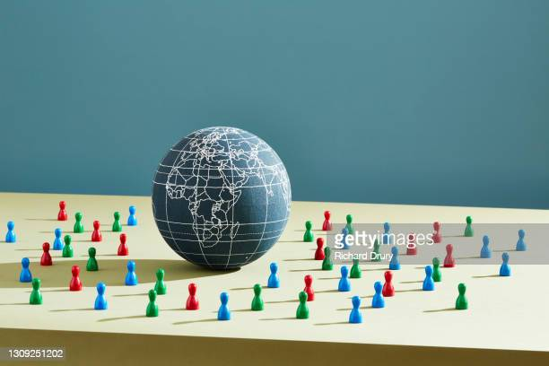 a world globe surrounded by people figurines - richard drury stock pictures, royalty-free photos & images