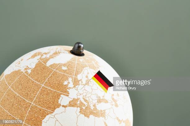 a world globe with a german flag pin showing germany - richard drury stock pictures, royalty-free photos & images