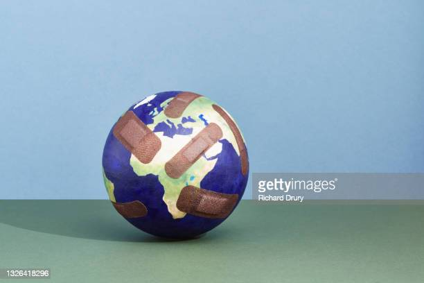 a world globe with band-aids - temporary stock pictures, royalty-free photos & images