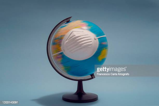 world globe with protective mask - epidemia foto e immagini stock