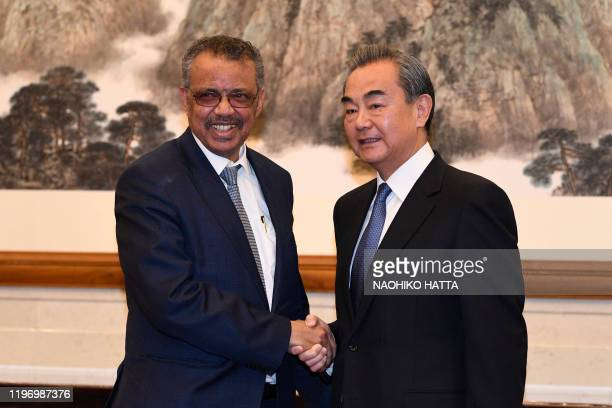 World Health Organization director general Tedros Adhanom shakes hands with Chinese State Councilor and Foreign Minister Wang Yi before a meeting at...
