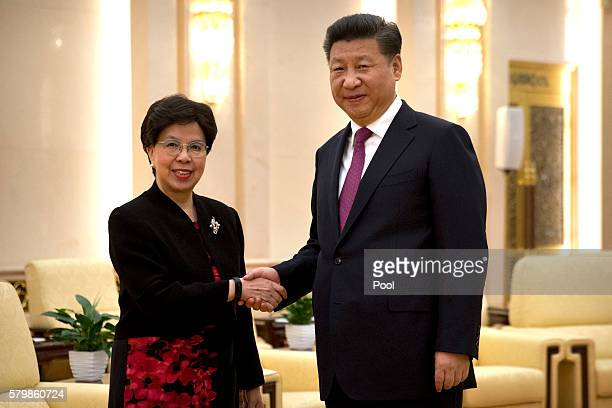 World Health Organization DirectorGeneral Margaret Chan left and Chinese President Xi Jinping right shake hands as they pose for a photo before a...