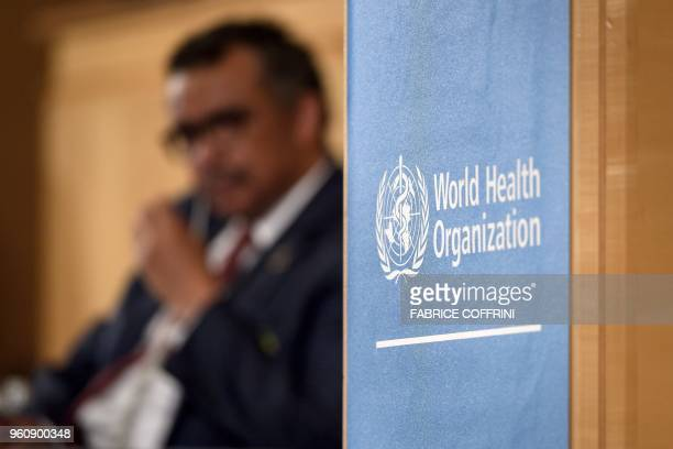 World Health Organization DirectorGeneral Tedros Adhanom Ghebreyesus is seen behind a sign of the WHO during the opening day of the World Health...