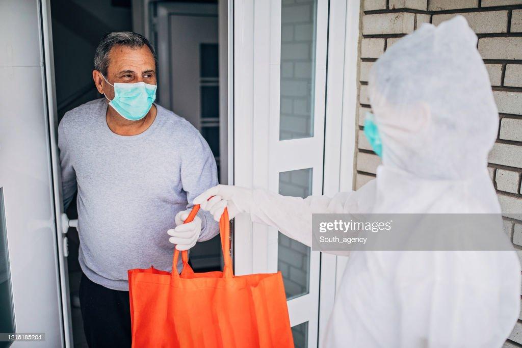 World health organization volunteer bringing groceries to a senior man at the front door : Stock Photo