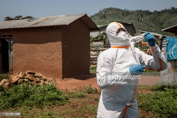 World Health Organization worker Belinda Landu changes her protective outfit after decontaminating the house of a pastor who has just tested positive...