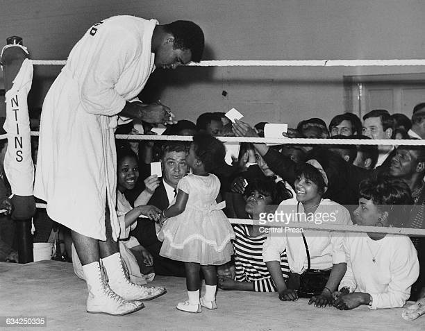 World heavyweight boxing champion Cassius Clay signs an autograph for two year-old Shelley Obermuller from Acton, during a training session at the...