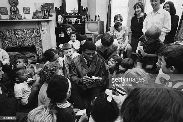 World heavyweight boxing champion Cassius Clay signs autographs during a visit to the London Free School children's play group and families' group at...
