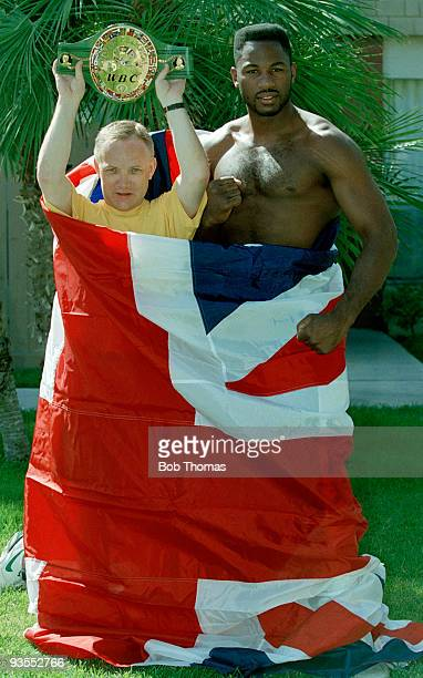 WBC World Heavyweight Boxing Champion Lennox Lewis of Great Britain with his manager Frank Maloney holding the WBC Title belt and wrapped in a Union...