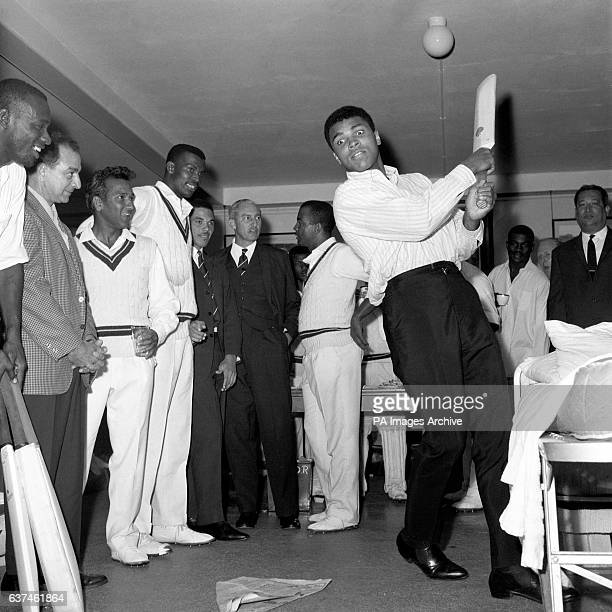 World Heavyweight Boxing Champion Muhammad Ali practises his batting technique in the West Indies dressing room to the amusemement of the cricketers