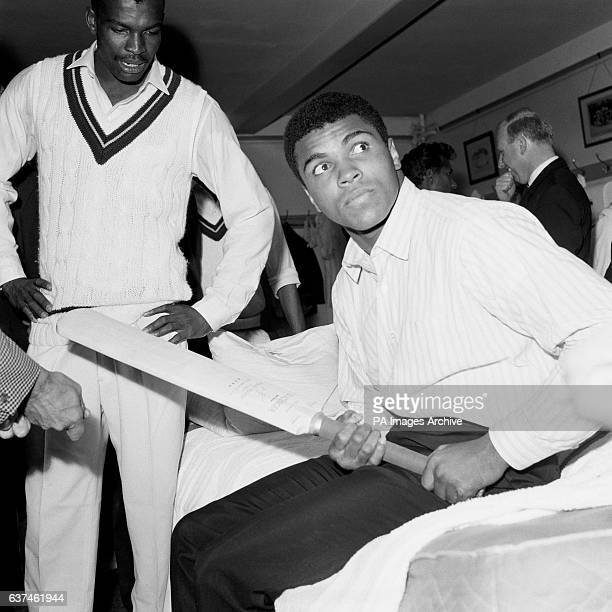 World Heavyweight Boxing Champion Muhammad Ali tries using a baseball grip on a cricket bat during a visit to the West Indies dressing room