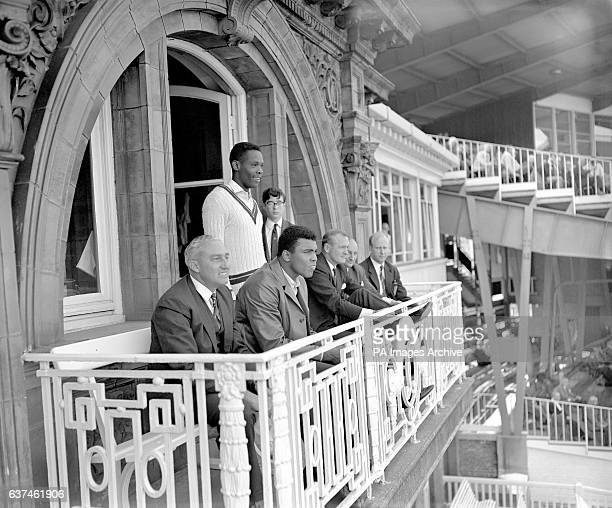 World Heavyweight Boxing Champion Muhammad Ali watches the match with West Indies team manager Jeffrey Stollmeyer from the West Indian dressing room...