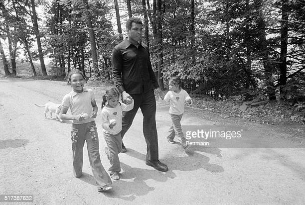 World heavyweight champ Muhammad Ali holds the hands of his twin daughters Jamalliah and Rahshoda as his daughter Miriam runs alongside at his...