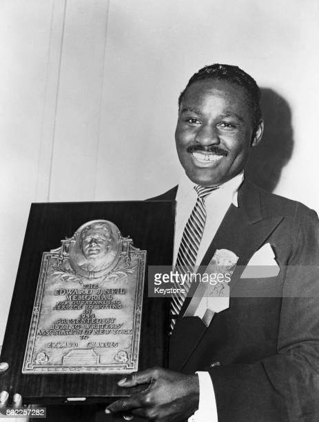 World Heavyweight Champion Ezzard Charles receives the Edward J Neil Memorial Boxing Plaque for outstanding service to boxing from the Boxing...